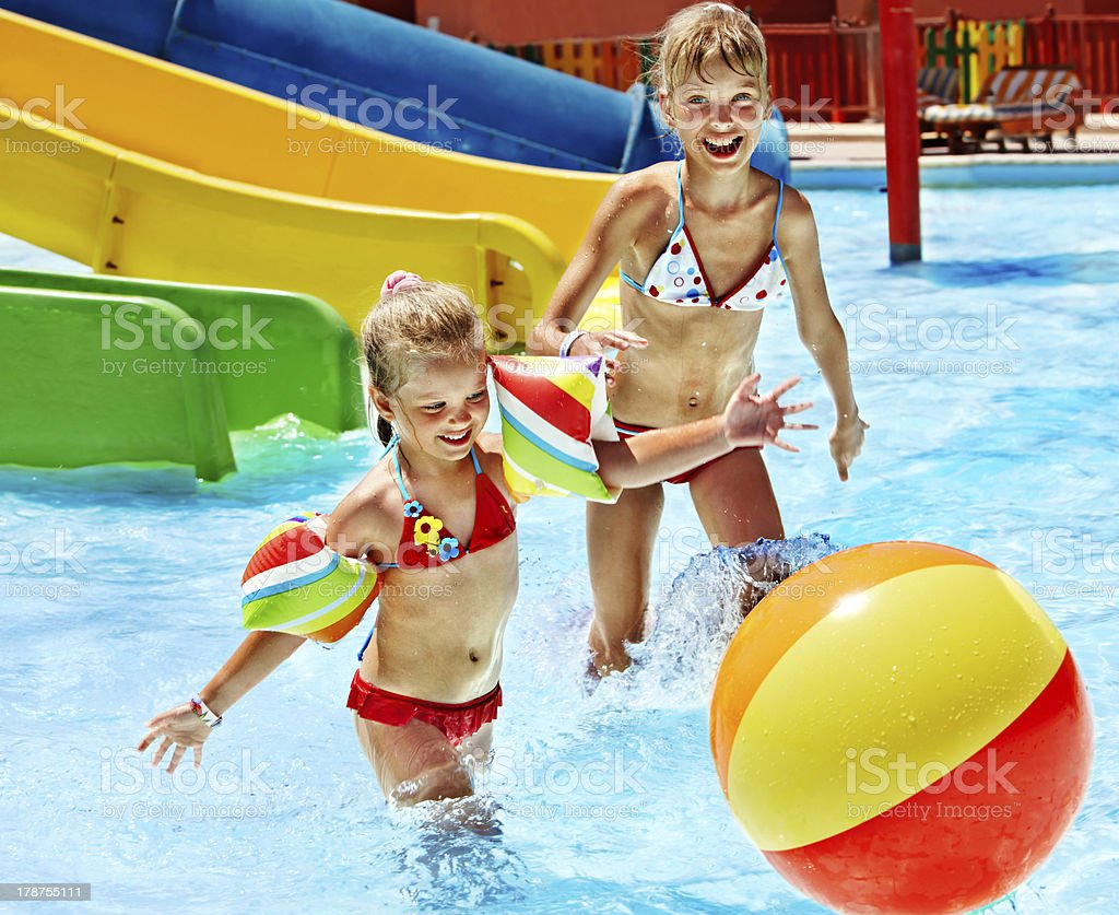 Two girl children with a beach ball playing at a water park royalty-free stock photo