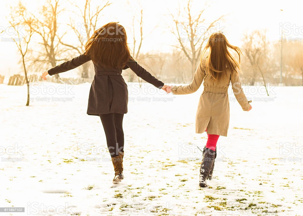 Two girl friends laughing, arms around each other and walking stock photo