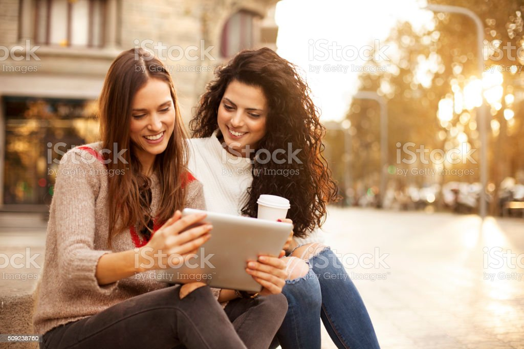 Two girl friends laughing at tablet outdoors street stock photo