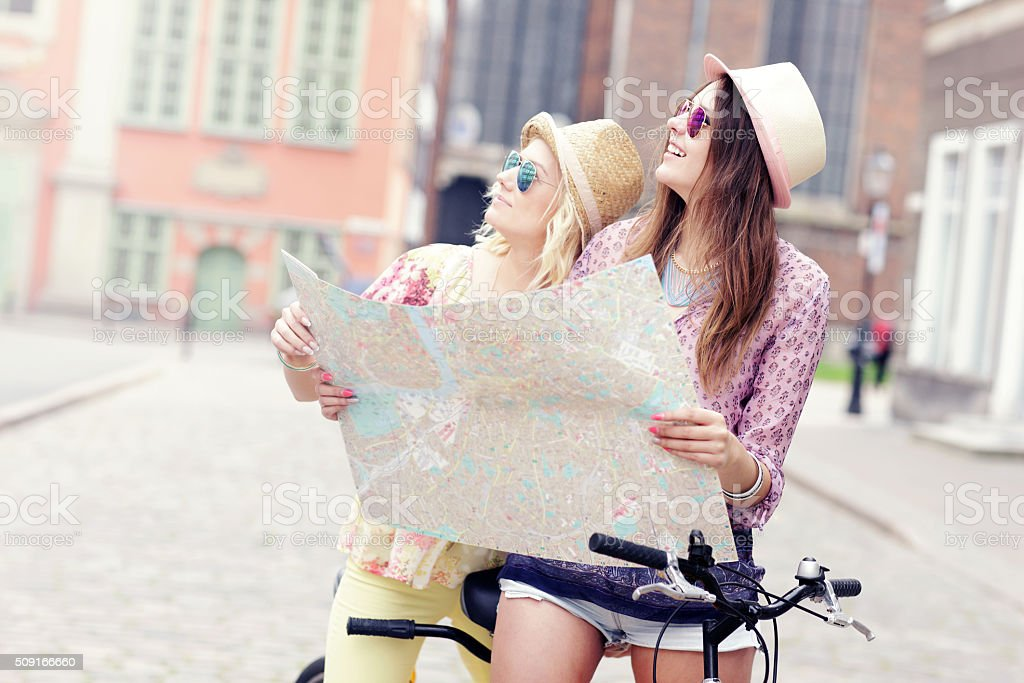 Two girl friends using map while riding tandem bicycle stock photo