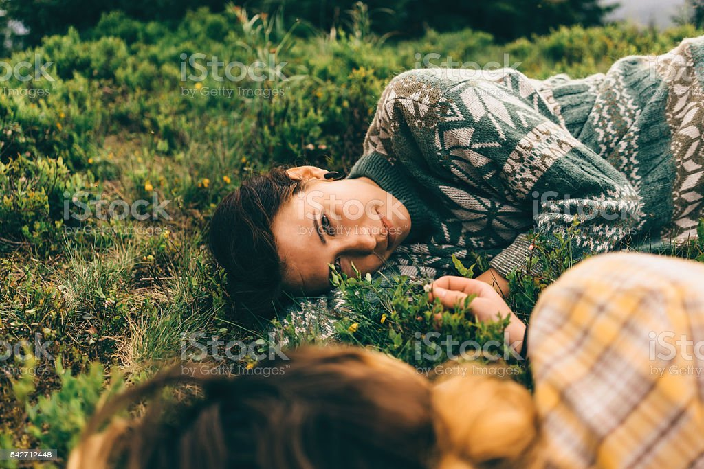 Two girl laying on the ground stock photo