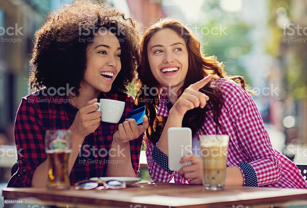 Two girlfriends are making fun in the cafeteria stock photo