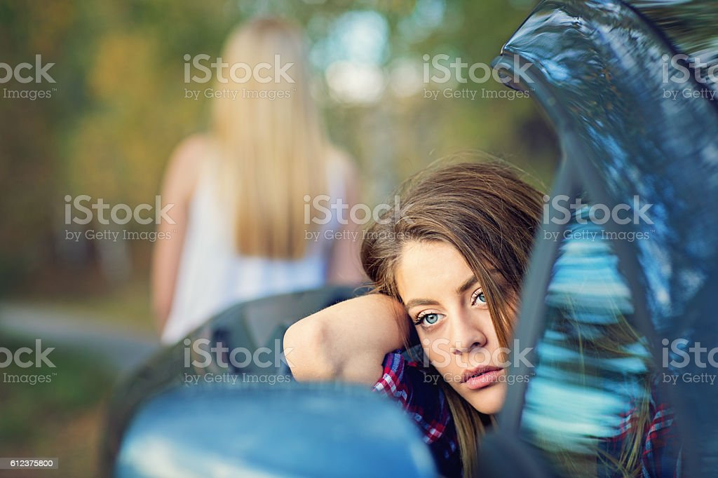 Two girlfriends are standing upset on the road stock photo