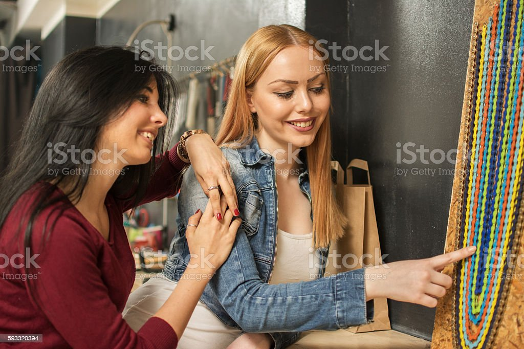 Two girlfriends choosing colorful bicycle chains. stock photo