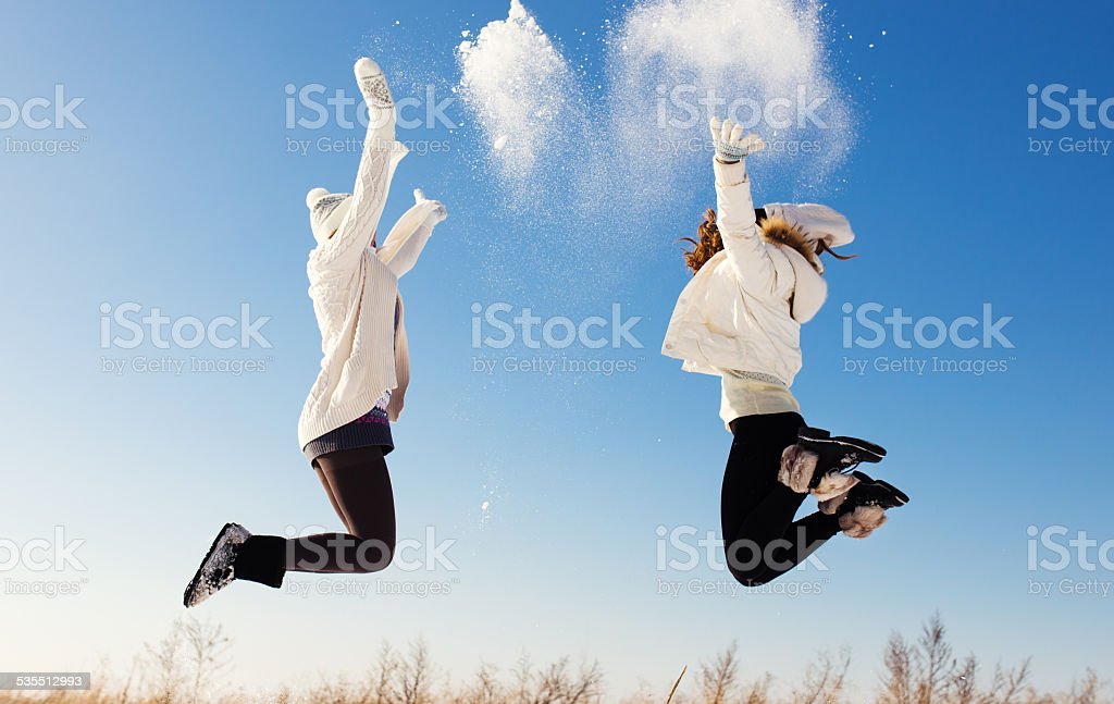Two girlfriends have fun and enjoy fresh snow stock photo