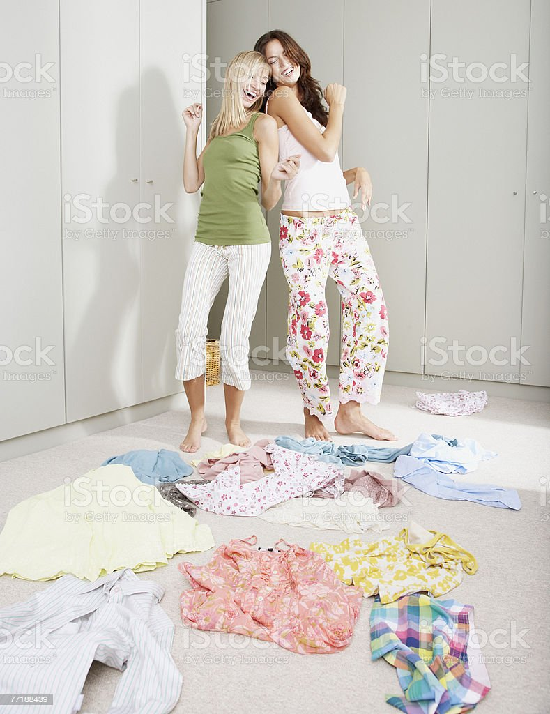 Two girlfriends in a bedroom going through a closet royalty-free stock photo
