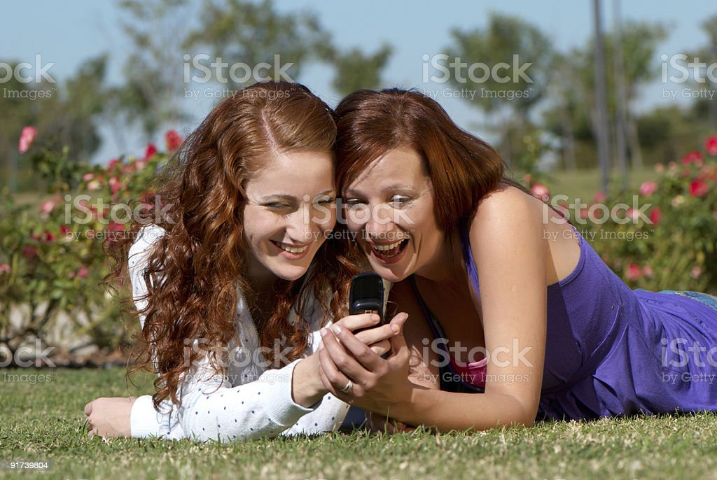 Two girlfriends in park with a mobile phone royalty-free stock photo