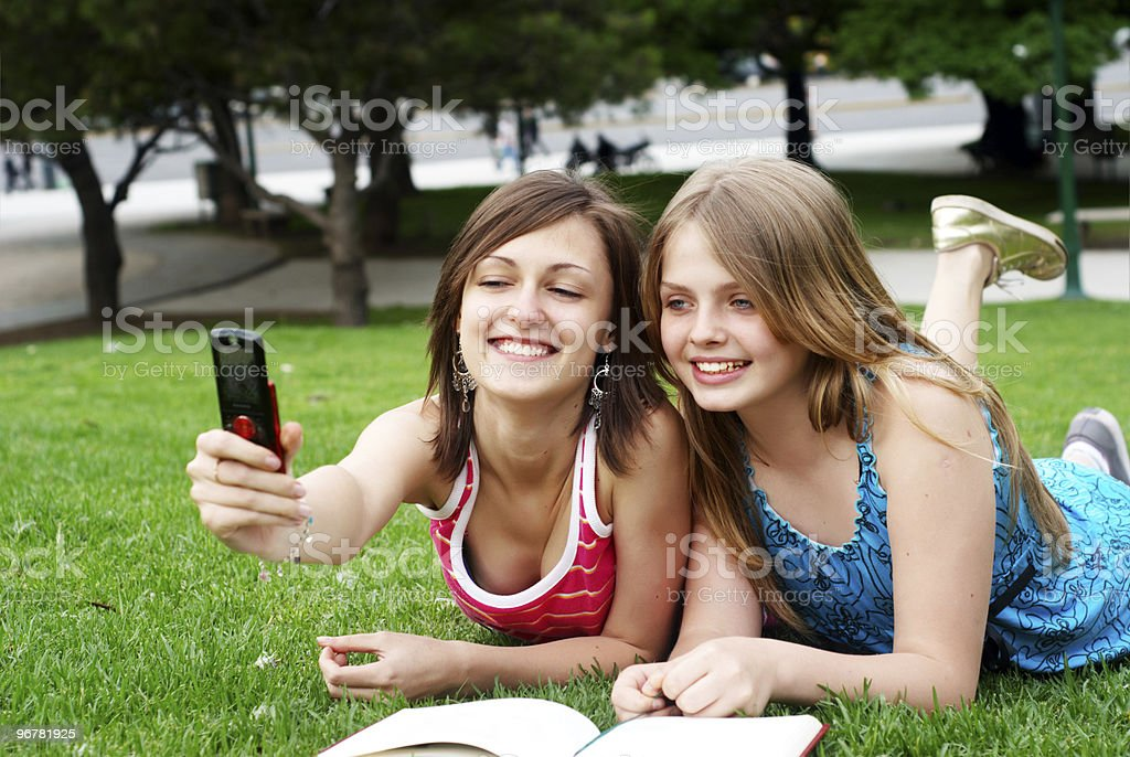Two girlfriends in park with a mobile phone stock photo