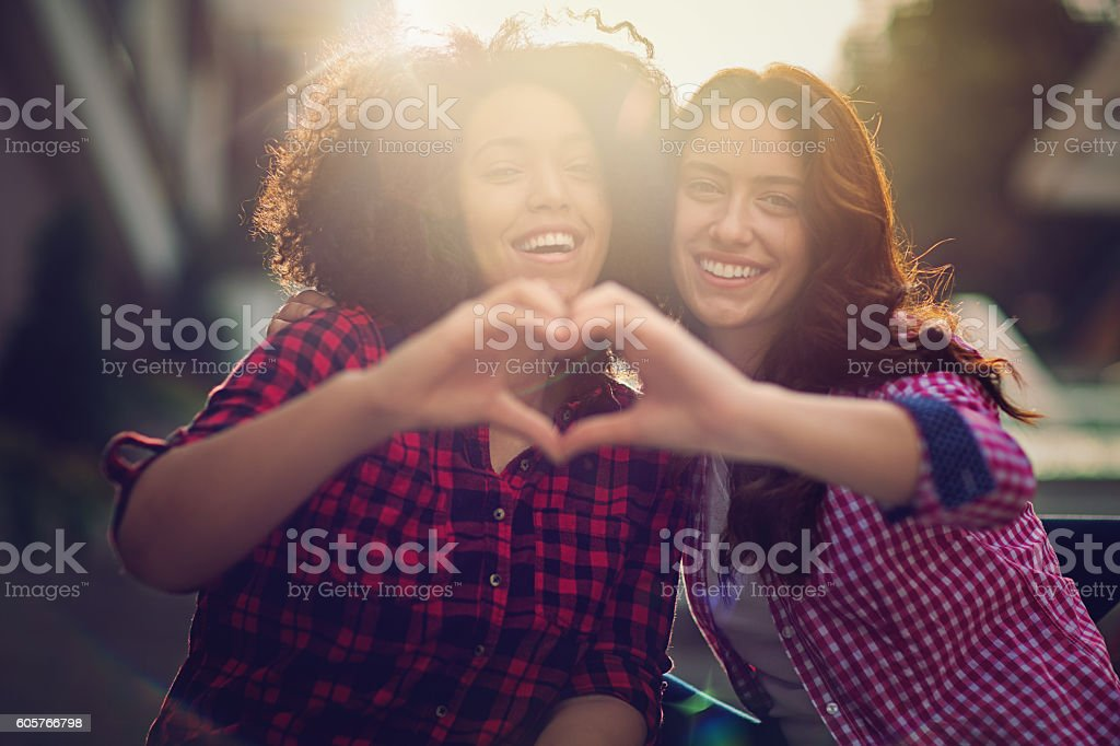 Two girlfriends making heart with their hands stock photo