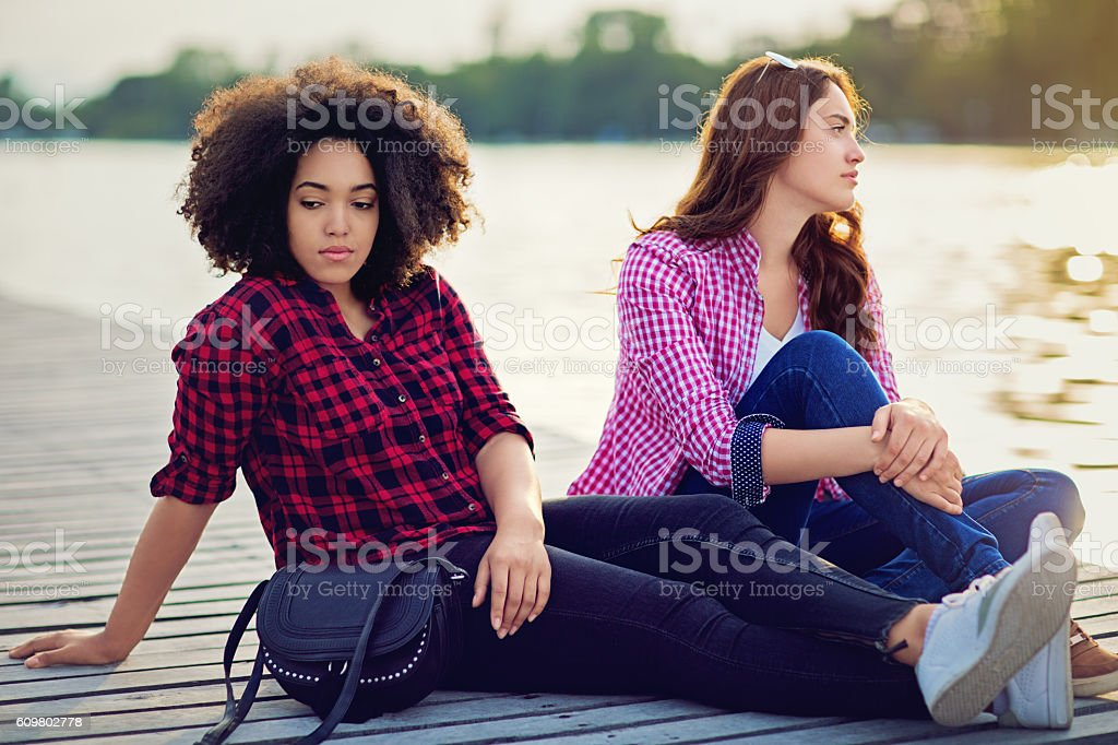 Two girlfriends on the lake with relationship difficulties stock photo