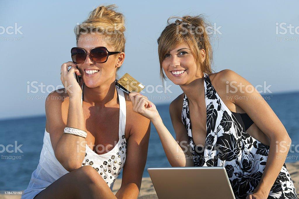 Deux copines shopping en ligne sur la plage. photo libre de droits