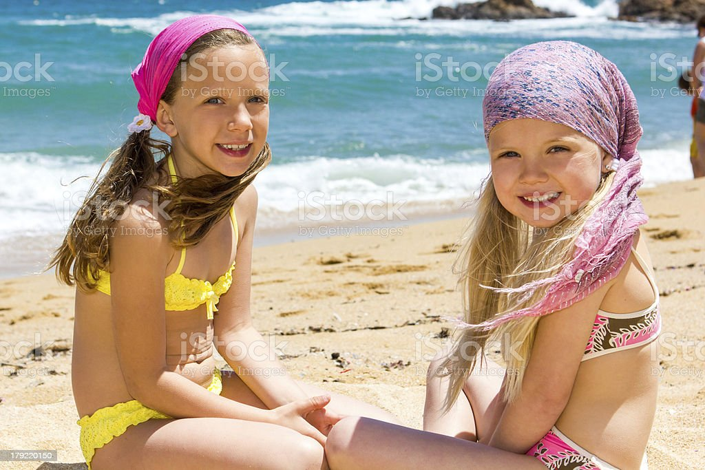 Two girlfriends sitting on beach. royalty-free stock photo