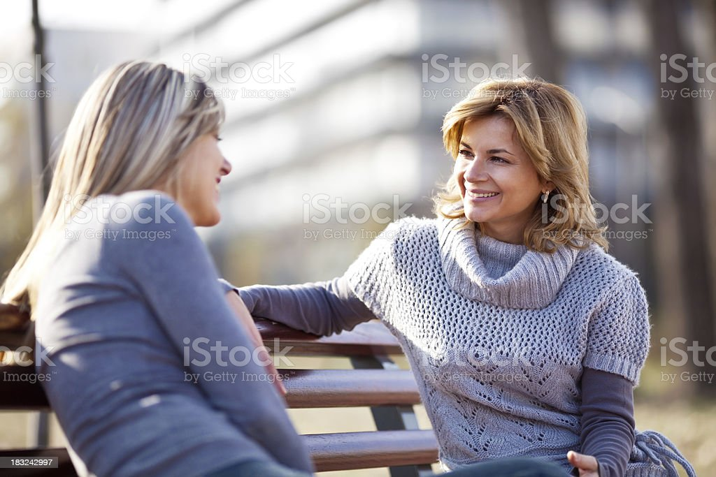 Two girlfriends sitting on park bench and talking royalty-free stock photo