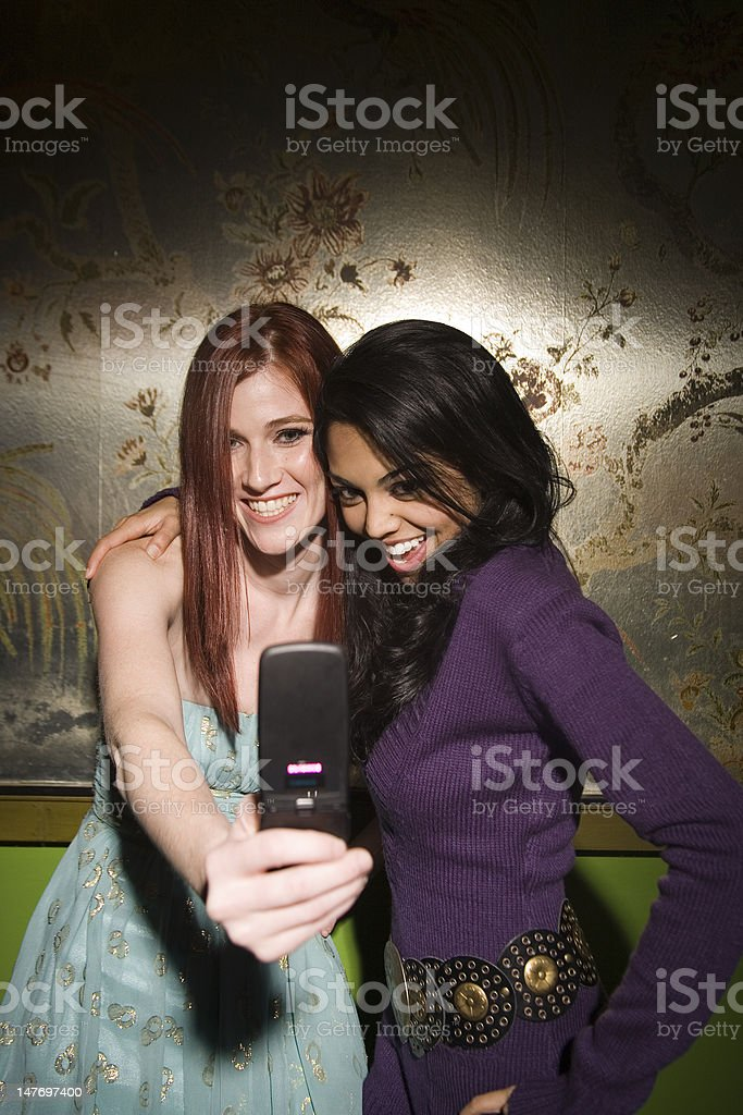 Two girlfriends taking a cell phone picture of themselves. royalty-free stock photo
