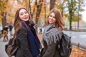 Two girlfriends walking in autumn park