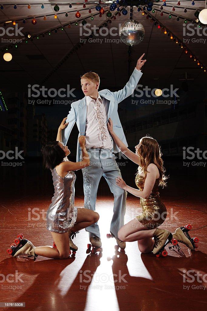 Two girls adoring roller skater, 70s style disco fever stock photo