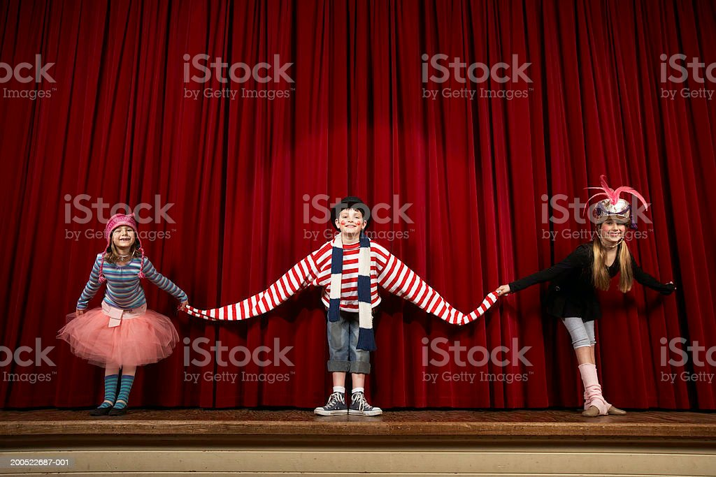 Two girls and boy in costume taking bow on stage, smiling