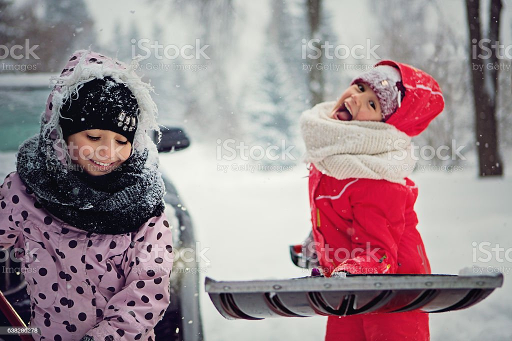 Two girls are cleaning the snow stock photo