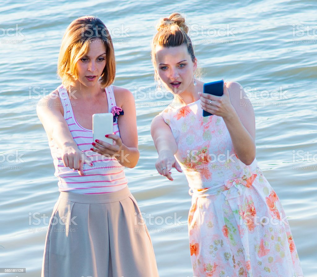 Two girls are playing with smart phones ner the river stock photo