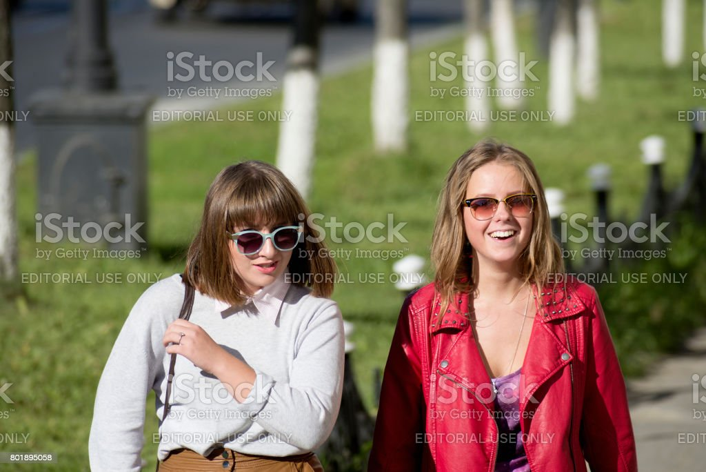 Two girls are walking along the sidewalk in the city of Magadan (Eastern Siberia). stock photo