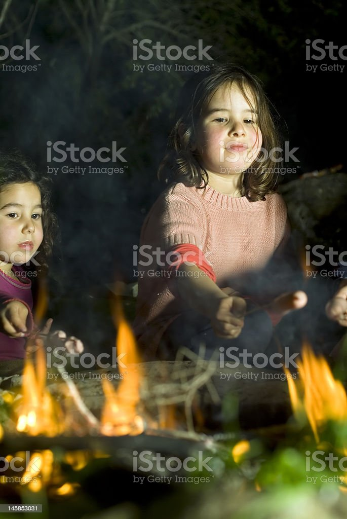 two girls at a bonfire royalty-free stock photo