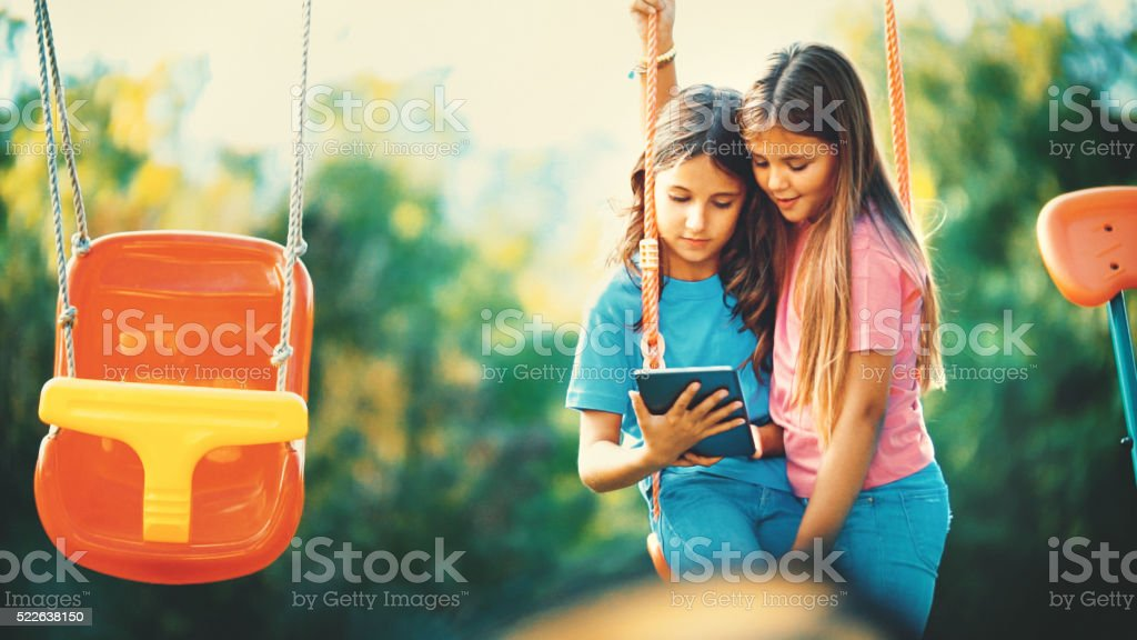 Two girls at a playground. stock photo