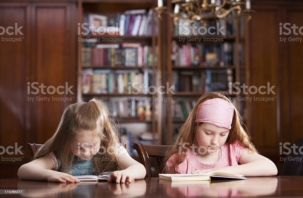 Two girls at the table reading royalty-free stock photo