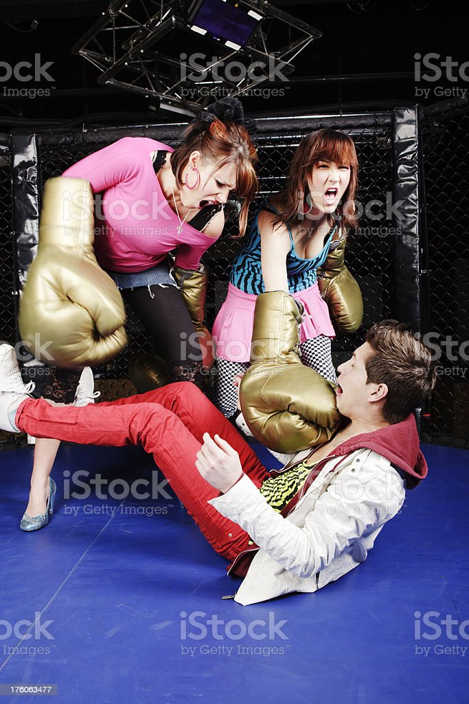 Two girls attacking defenseless guy with supersized boxing gloves royalty-free stock photo