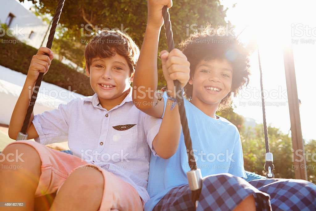 Two Girls Boys Fun On Swing In Playground stock photo