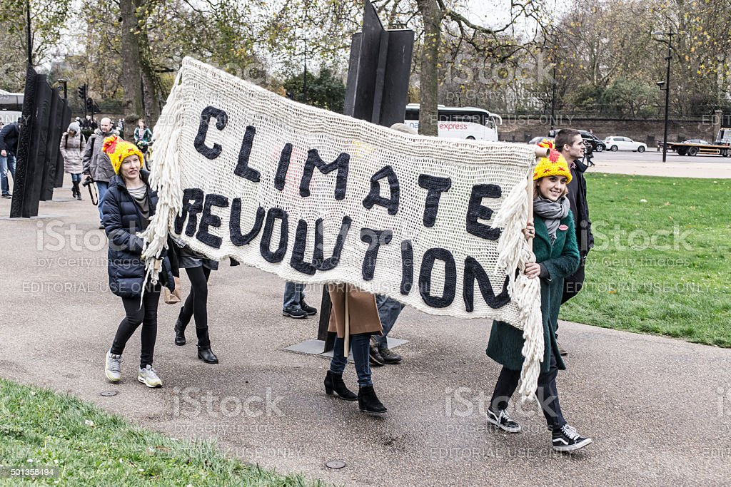 Two girls carrying a big billboard with words 'Climate revolution' stock photo
