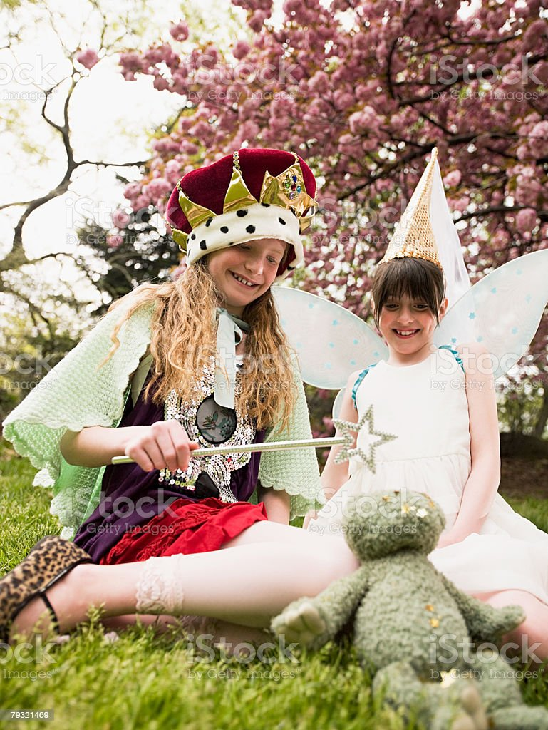 Two girls casting a spell on a soft toy royalty-free stock photo