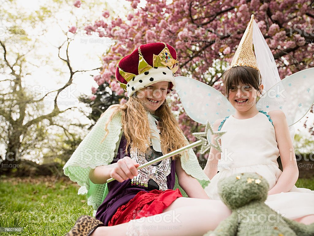 Two girls casting a spell on a soft toy stock photo