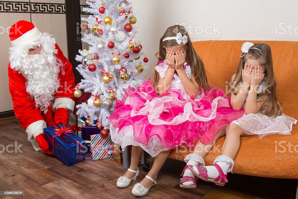 Two girls closed eyes with his hands until Santa Claus stock photo
