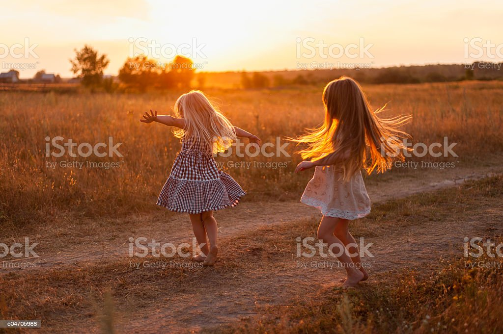 two girls dancing in a field at sunset stock photo