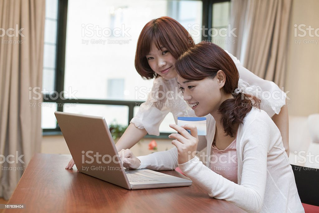 Two girls doing online shopping with laptop royalty-free stock photo