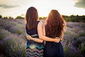 Two girls enjoying sunset in lavender field