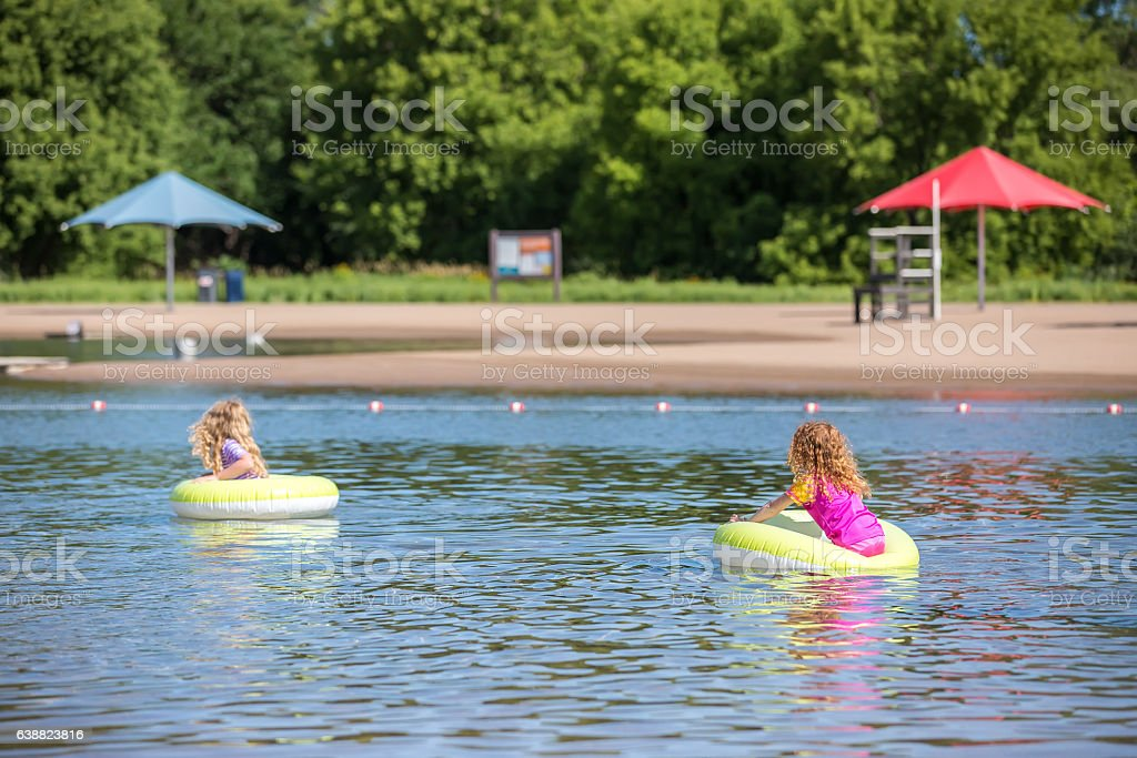Two Girls Floating on Inner Tubes At Swimming Beach stock photo