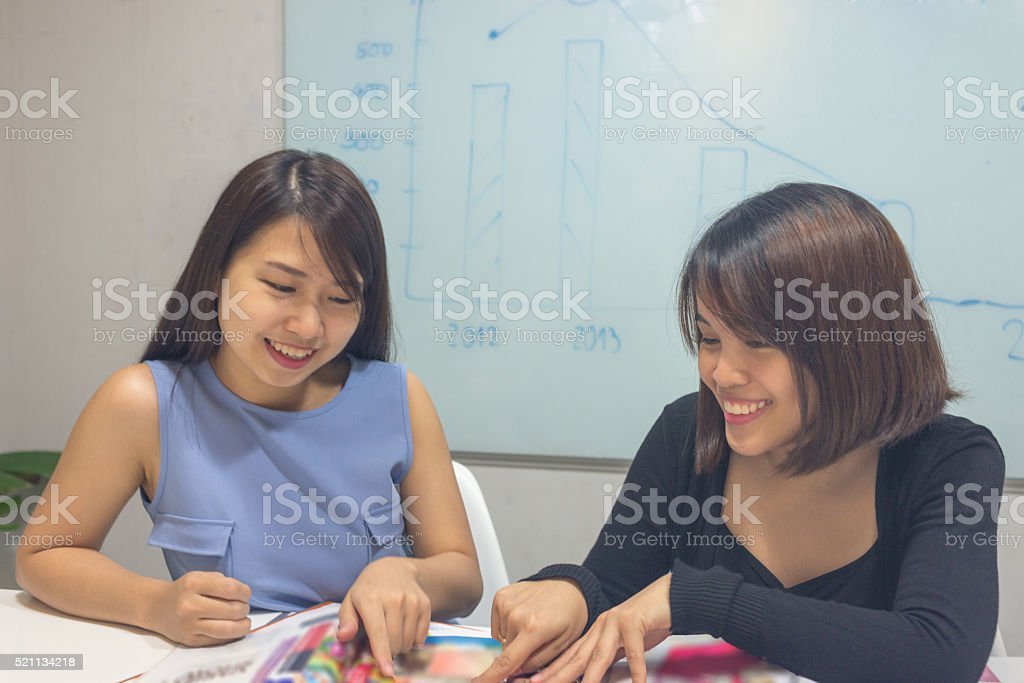 Two girls gossiping at workplace about a fashion magazine stock photo