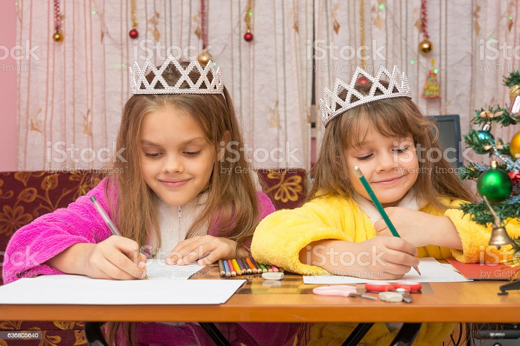 Two girls happily writing a letter to Santa Claus sitting stock photo