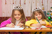 Two girls happily writing a letter to Santa Claus sitting