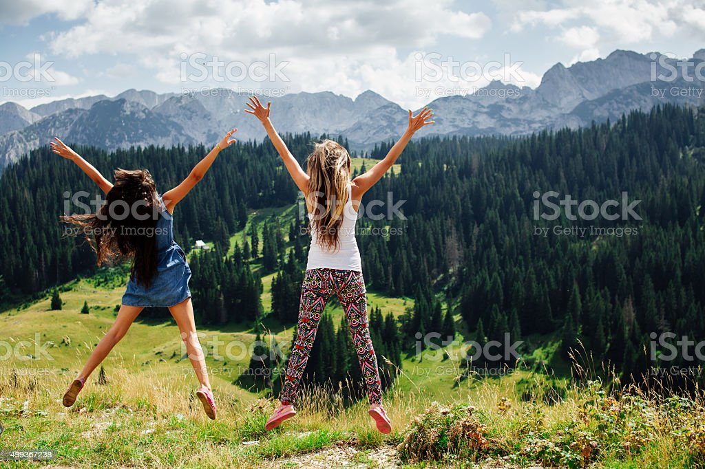 two girls happy jump in mountains stock photo
