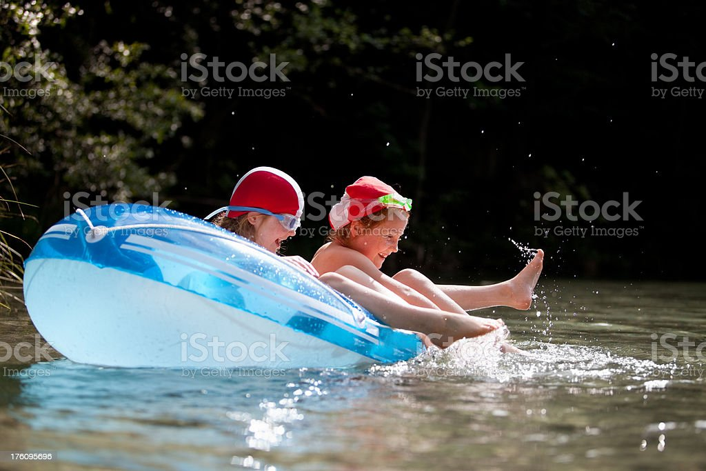Two girls having fun in a rubber dinghy royalty-free stock photo