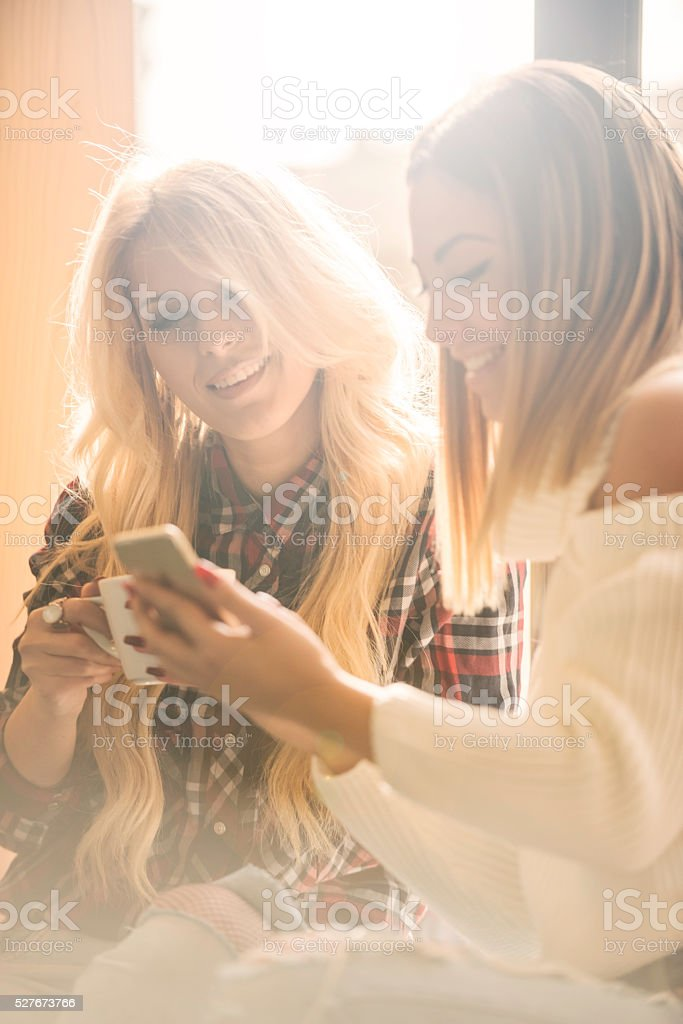 Two girls having fun while drinking coffee stock photo