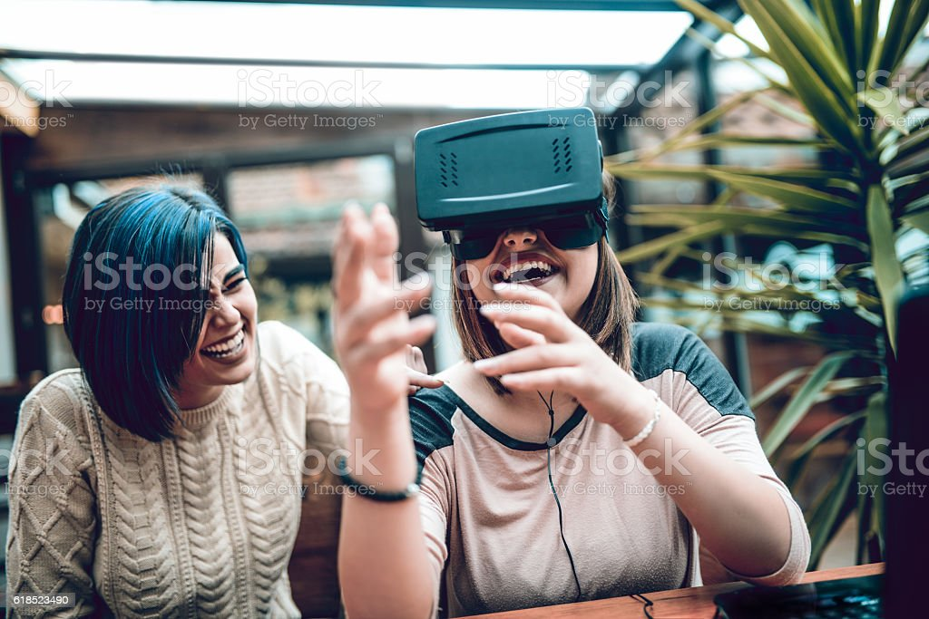 Two Girls Having Fun with Virtual Reality Simulator in Cafe stock photo