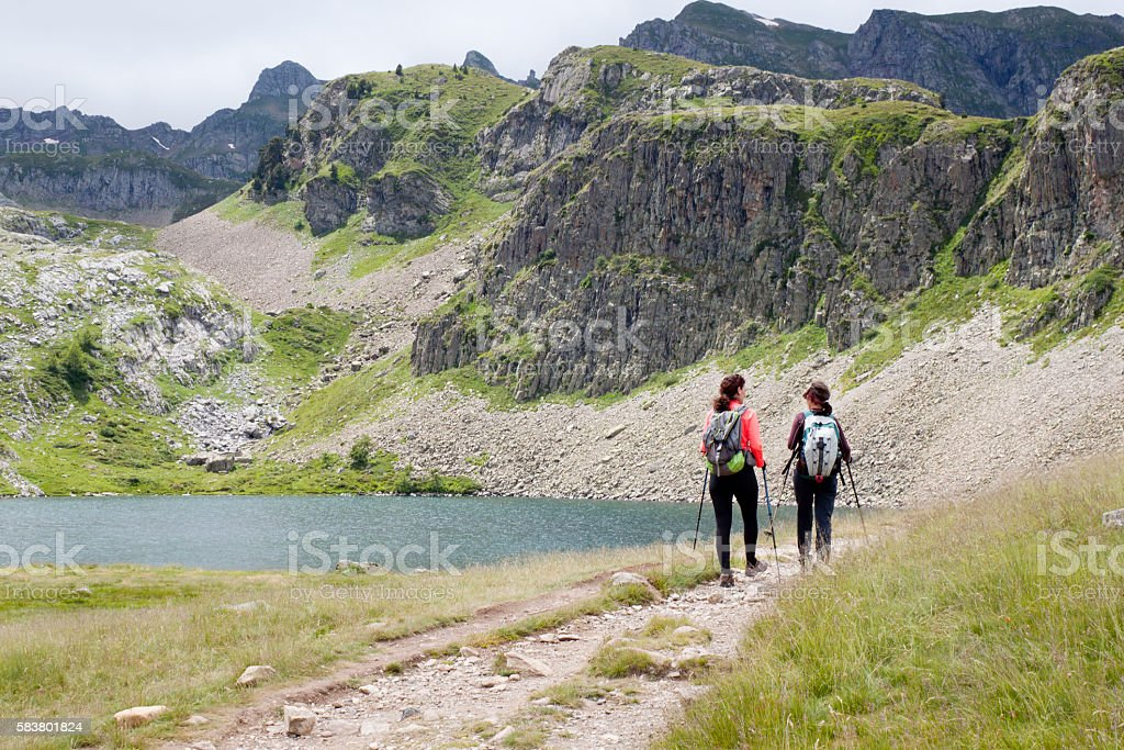 Two girls hiking in the Ayous Lakes Pyrenees, France stock photo