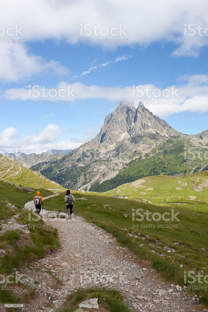 Two girls hiking with the Midi d'Ossau peak behind stock photo