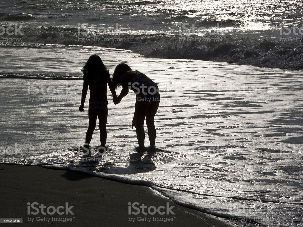 Two girls hold hands and wade in ocean surf. stock photo
