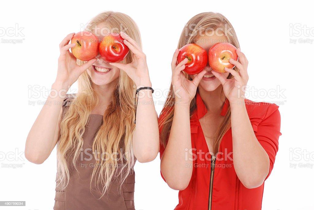 Two girls hold near eyes fresh apples stock photo