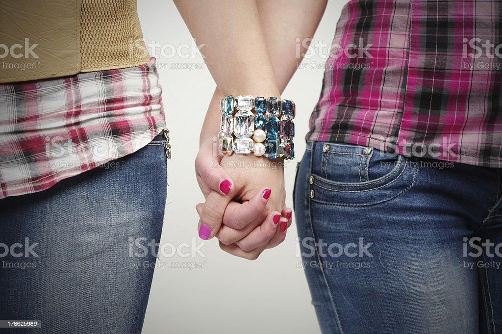 Two girls holding hands between their hips stock photo