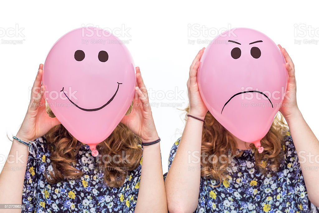 Two girls holding pink balloons with facial expressions for head stock photo